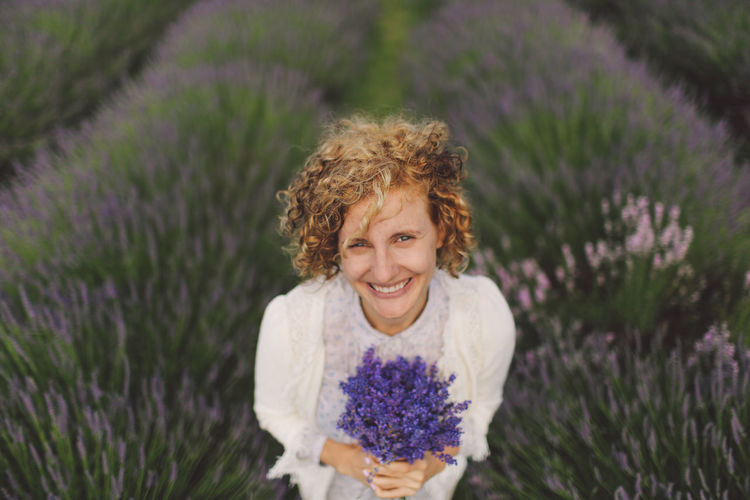 Portrait Of Cheerful Woman Holding Lavender Flowers On Field