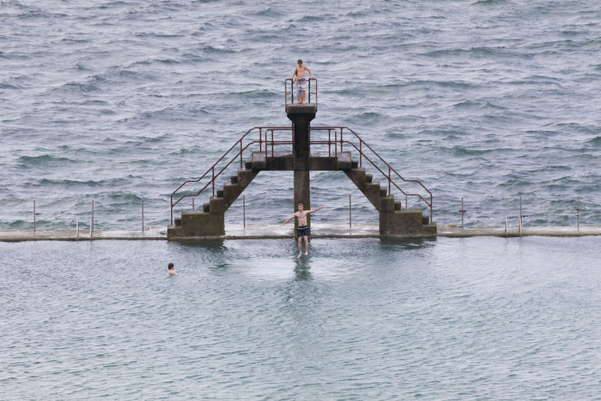 Young man jumping into seawater pool in Saint-Malo, France Aquatic Atlantic Ocean Board Challenge Competition Courage Diving Board Diving Platform Jump Jumping Mid-air Outdoors People Platform Pool Sea Sport Swimming Pool Swimwear Teenage Boys Vacations Water Young Adult Young Men Youth Of Today