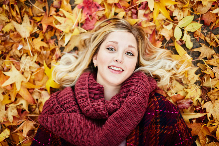 Portrait Of Young Woman Lying On Autumn Leaves