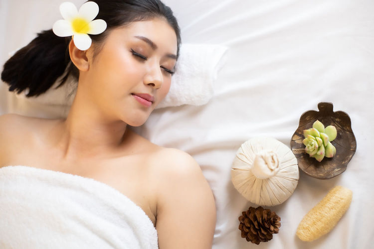 High angle view of woman wearing towel relaxing on bed in spa
