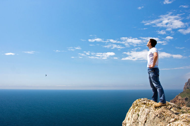 Man Standing On Rock Looking At Sky