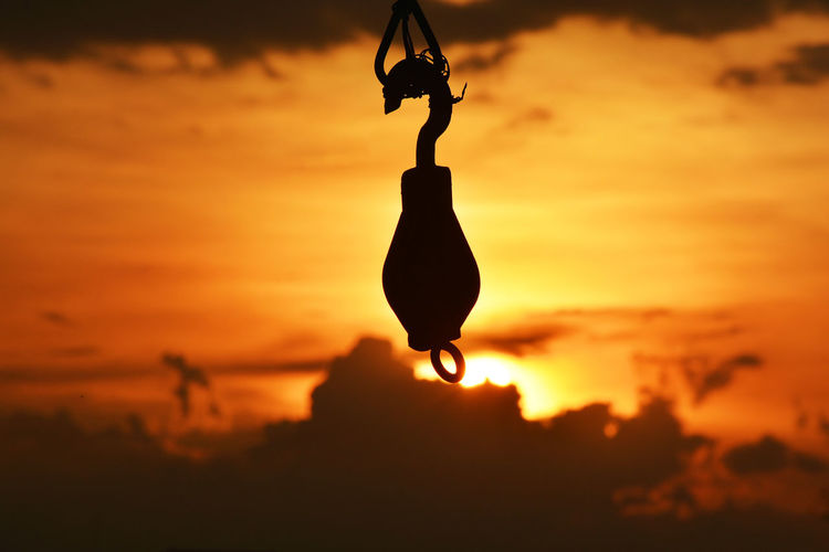 Close-up of silhouette person holding hanging against sky during sunset