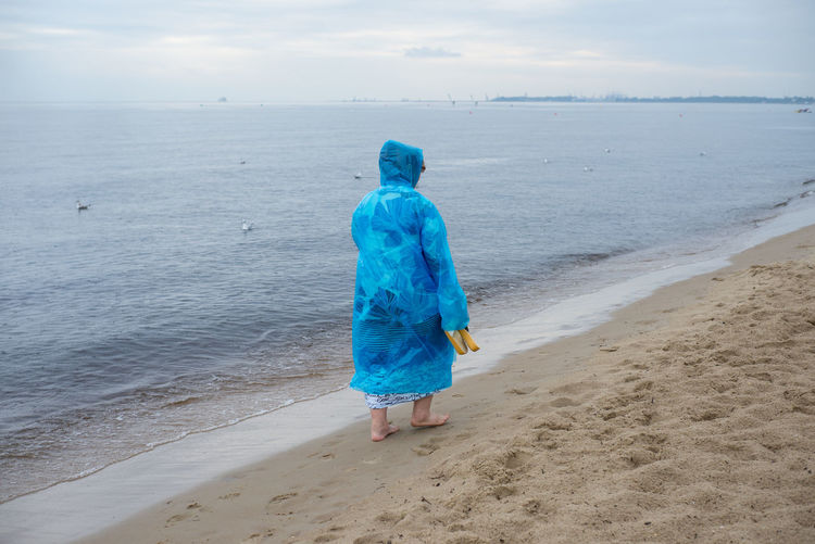 Woman In Raincoat Walking At Beach