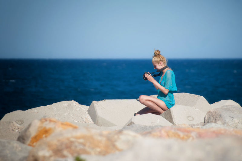 Side View Of Young Woman Looking At Camera While Sitting On Rocks By Sea