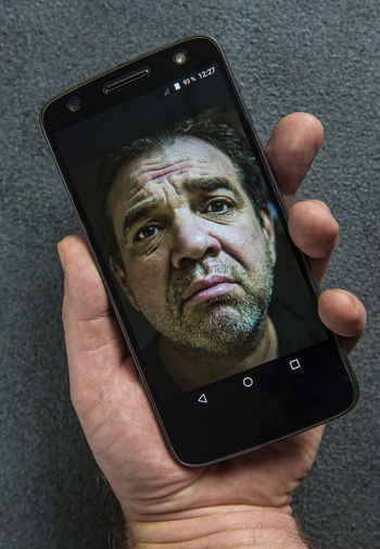 Cropped hand of man holding mobile phone with photograph
