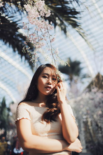 Low angle portrait of young woman standing by plants in park