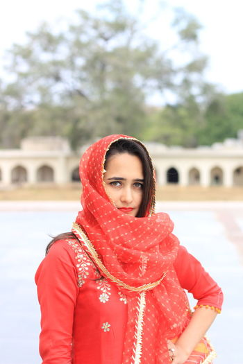 Young Adult Young Women One Person Red Portrait Looking At Camera Focus On Foreground Real People Clothing Standing Lifestyles Architecture Women Day Built Structure Waist Up Leisure Activity Front View Warm Clothing Beautiful Woman Outdoors Scarf Hairstyle