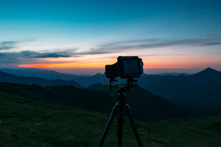 View of camera on landscape against sky during sunset