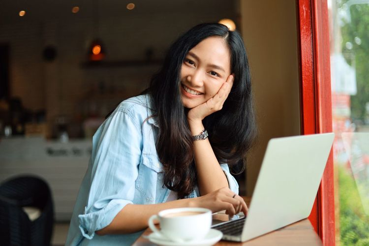 Sitting Smiling Wireless Technology Technology Laptop Adult Computer Young Adult Women Using Laptop One Person Portrait Happiness Long Hair Cafe Communication Hair Cup Young Women Mug Hairstyle Black Hair Beautiful Woman