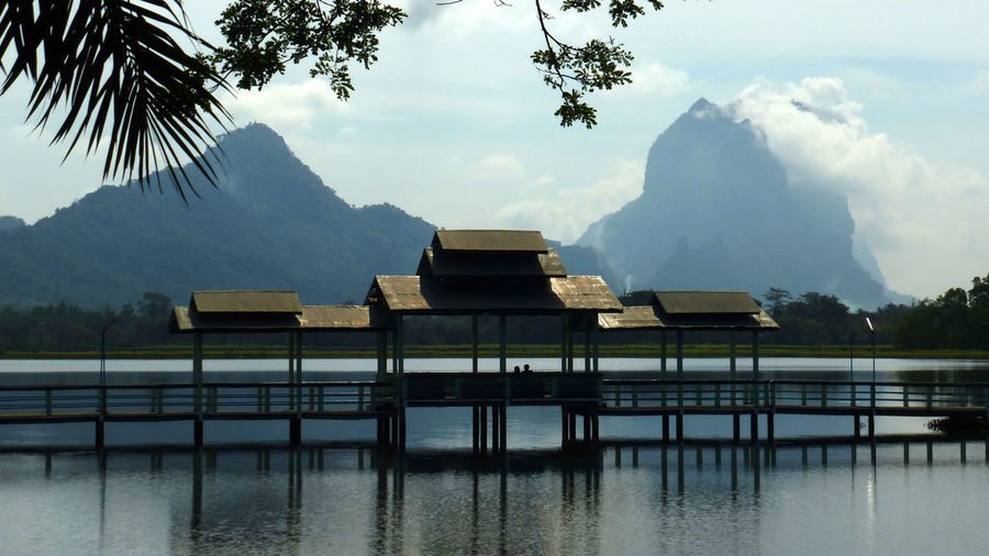 Built structure by lake against sky
