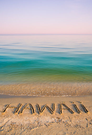 Hawaii Text On Sea Shore Against Clear Sky