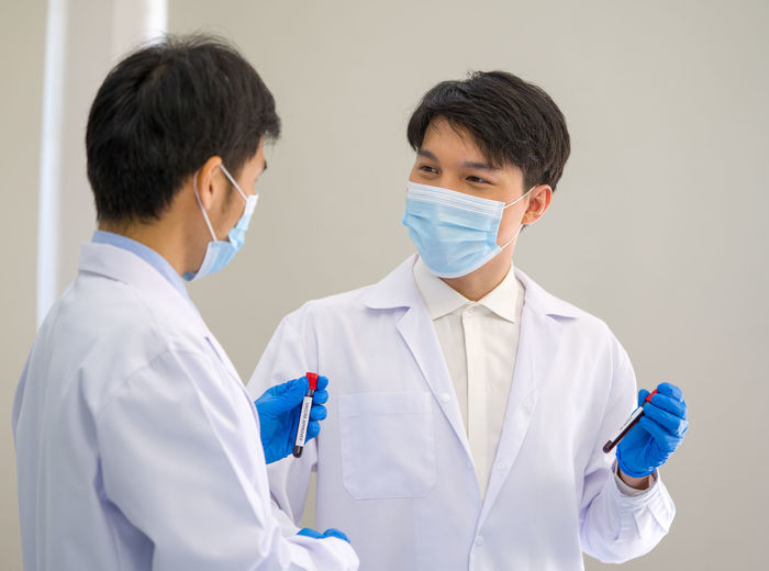 Scientists wearing mask standing in laboratory