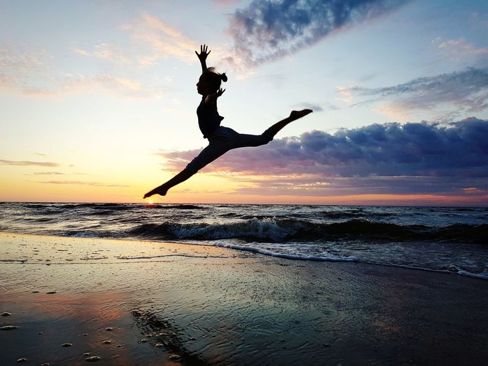 Young Woman Jumping On Shore At Beach Against Sky During Sunset
