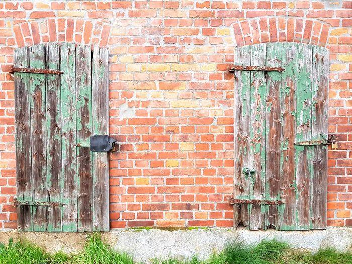 Closed door on brick wall of building