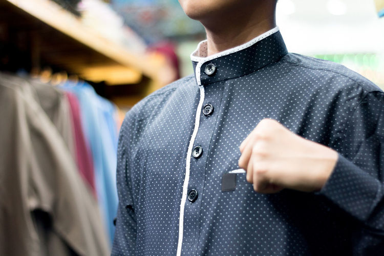 Midsection of boy wearing spotted shirt at store