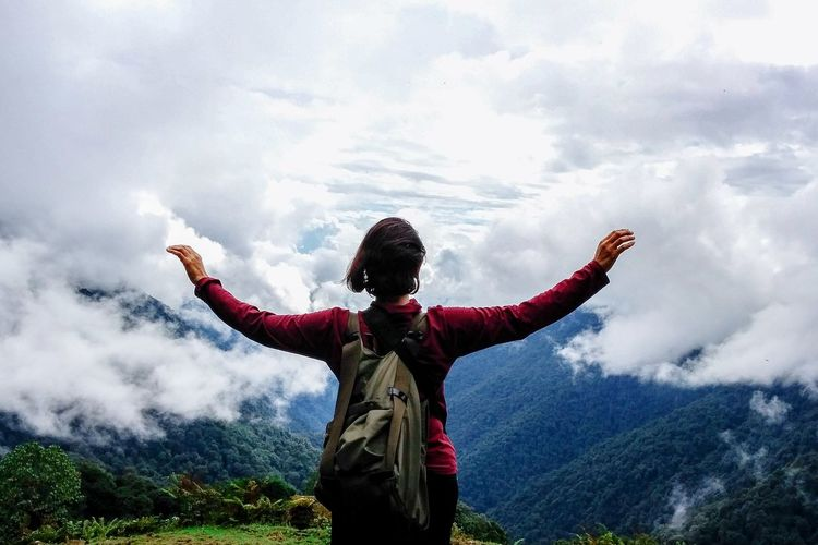 Rear view of woman with arms outstretched standing against cloudy sky