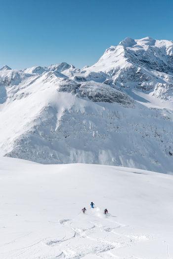Group of people skiing in fresh powder snow in vast alpine landscape, gastein, austria.