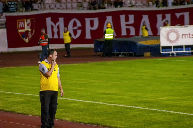 Full length of man standing on soccer field