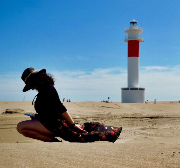 Land Sky One Person Beach Leisure Activity Full Length Sitting Built Structure Nature Building Exterior Outdoors Architecture Lighthouse Lifestyles Guidance Tower Real People Sand Sea Women
