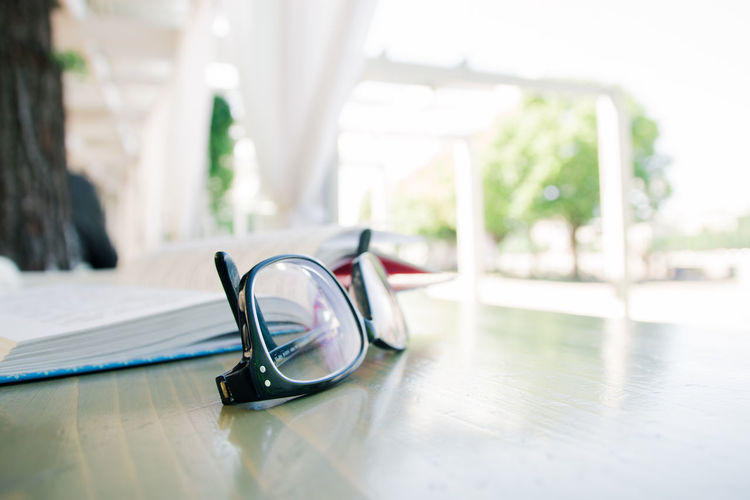 book and glasses Table Indoors  Glasses Day Still Life Glass - Material No People Focus On Foreground Eyeglasses  Wood - Material Transparent Close-up Absence Selective Focus Personal Accessory Reflection Flooring Window Sunlight Surface Level
