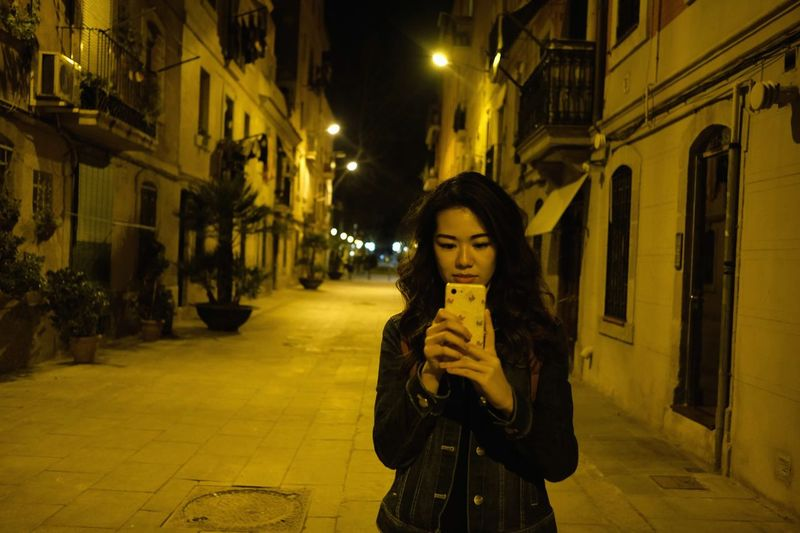 Portrait of young woman standing on street at night