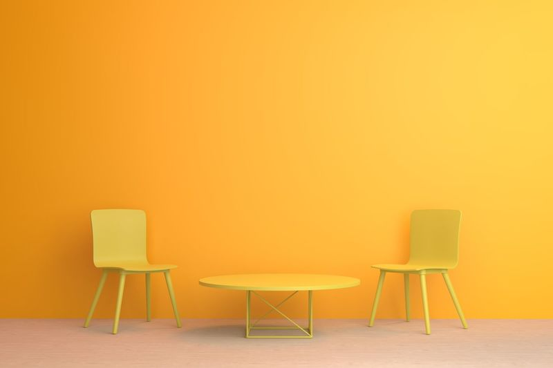 Empty chairs and table against on floor against wall