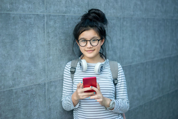 Portrait of teenage girl holding smart phone while standing against wall