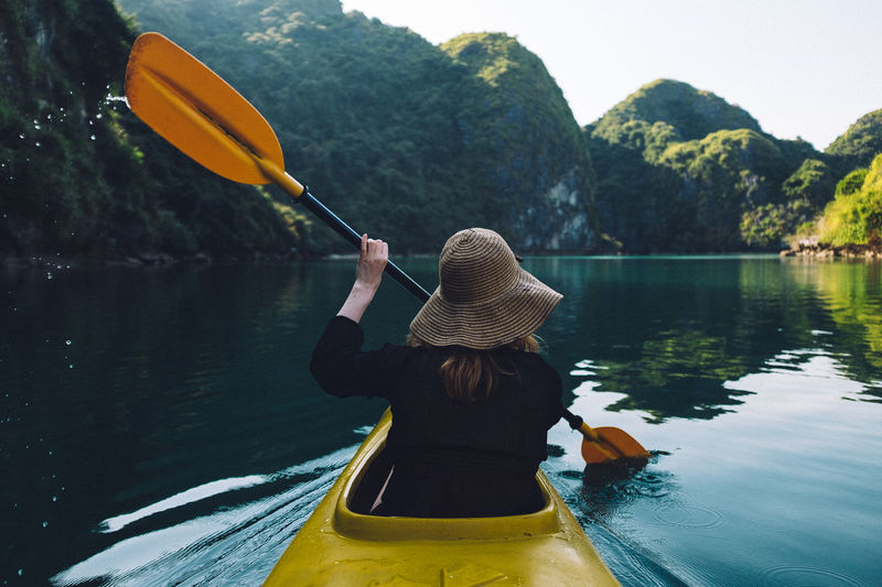 In the calm waters of Vietnam's Halong Bay. Famous Halong Bay  Hat Vietnam Beauty In Nature Day Hairstyle Holding Instagram Kayak Leisure Activity Lifestyles Nature Nautical Vessel Oar One Person Outdoors Paradise Real People Rear View Transportation Tree Water Women Yellow