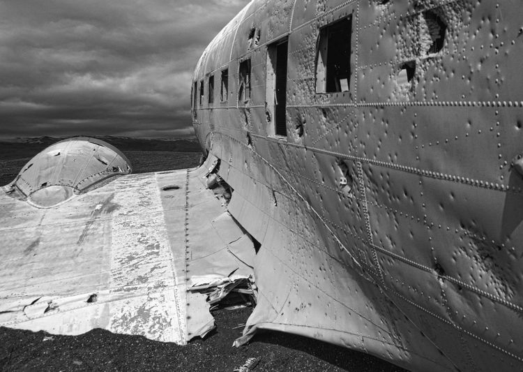 Close-Up Of Abandoned Airplane At Beach Against Cloudy Sky