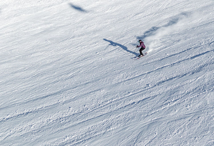 Aerial view of woman skiing on snowcapped mountain