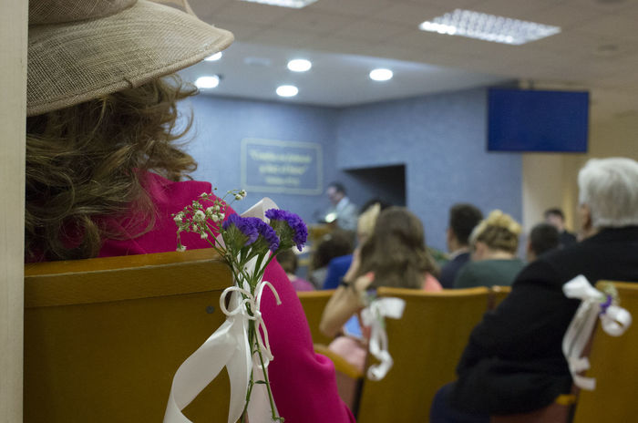 Wedding Wedding Photography Wedding Photographer Wedding Day Guests Wedding Guests Sat Down Awaiting That Special Moment In The Crowd Spectating Kingdom Hall Attention To Detail Big Hat Spanish Spanish Wedding Spanish Culture Flowers Bouquet