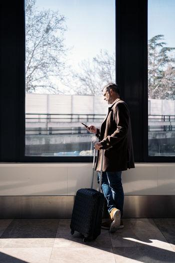 Full length of man using phone on window