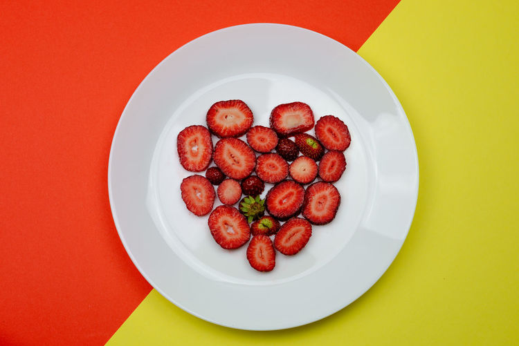 Creative Valentine Day romantic concept composition flat lay top view with heart strawberries on a white plate isolated on a orange and yellow background. Food And Drink Food Freshness Red Indoors  Still Life No People Strawberry Strawberries Fruit Fruits Fresh Healthy Eating Natural Raw Vitamin Raw Food Tasty Breakfast Ripe Juicy Sweet Berry Delicious Nutrition Background Rustic Dessert Freshness Eating Organic Close-up Diet Ingredient Vegan Snack Apperitive Pattern Flat Flat Lay Heart Shape Valentine's Day  Valentine Romantic Concept Vegetable Directly Above Plate Table High Angle View Ready-to-eat Wellbeing