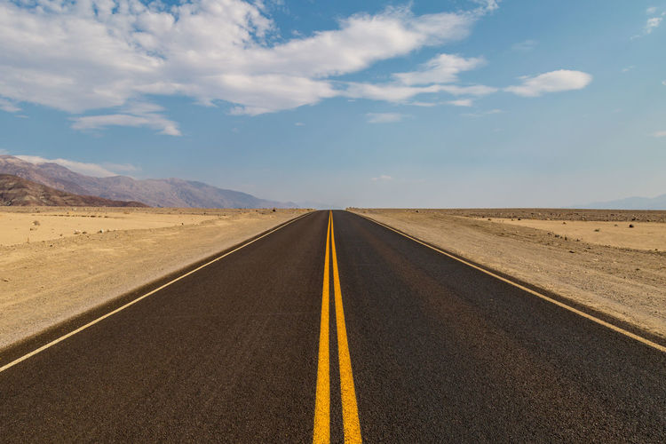 A newly resurfaced road in Death Valley, California Death Valley Arid Climate Climate Cloud - Sky Diminishing Perspective Direction Dividing Line Land Landscape Long Marking Nature No People Outdoors Road Road Marking Scenics - Nature Sign Sky Symbol The Way Forward Tranquil Scene Tranquility Transportation vanishing point