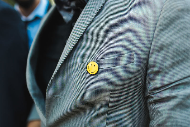 Midsection of man with anthropomorphic smiley face over pocket