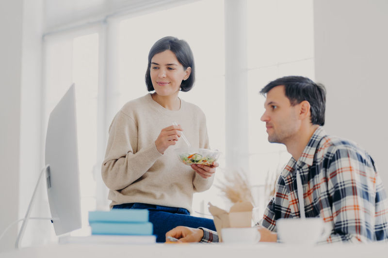 Couple using computer on table