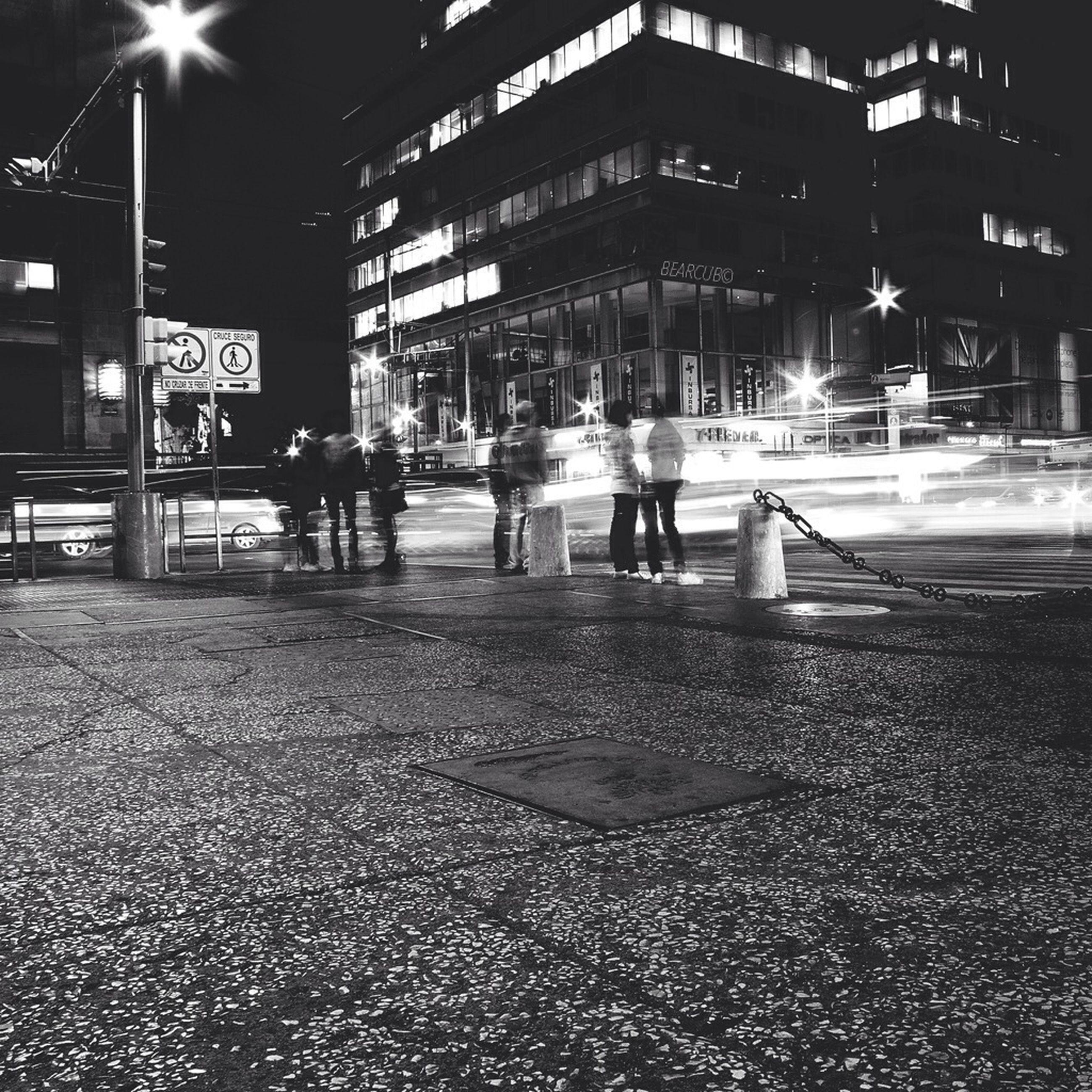building exterior, night, city, street, illuminated, architecture, built structure, city life, men, walking, city street, lifestyles, road, transportation, street light, person, outdoors, leisure activity, text