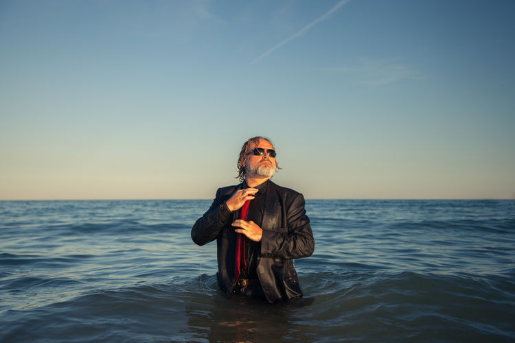 Well-dressed mature man standing in sea against clear sky during sunset