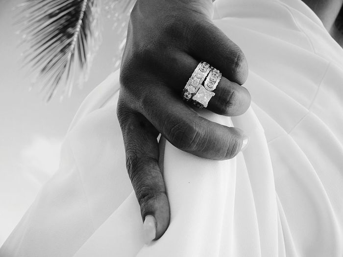 Cropped hand of bride holding dress