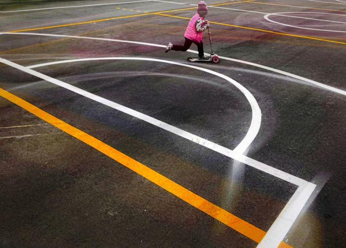 High angle view of man playing basketball on road