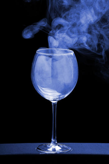 Close-up of wineglass against black background