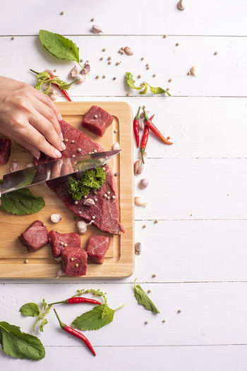 Cropped hand cutting meat at table