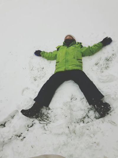 Full length of boy making snow angel on field