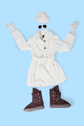 Directly above shot of winter clothing against blue background