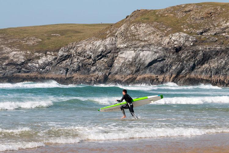 Full length of man surfing in sea against sky