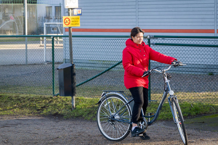 Side view of woman with bicycle against fence in city