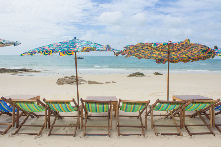 Chairs and parasols on beach against sky