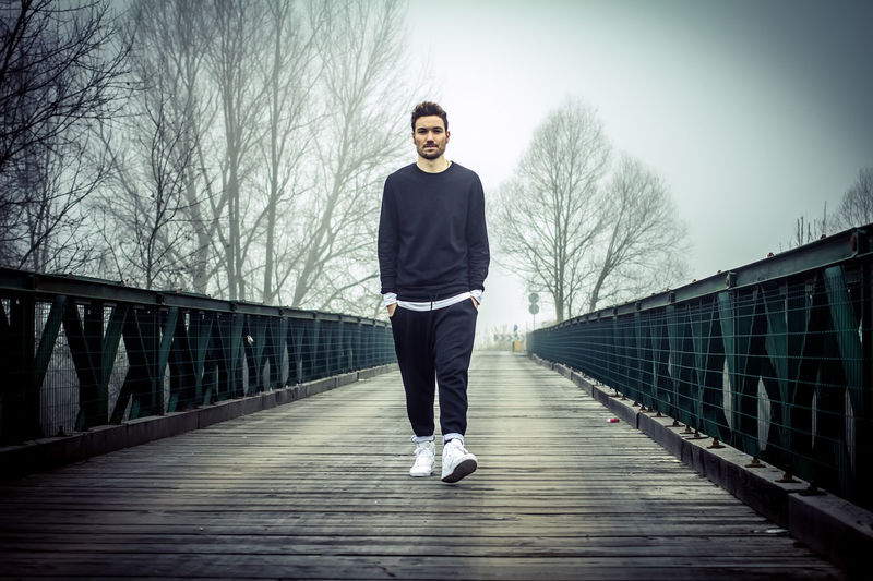 Young man walking on bridge against sky during foggy weather