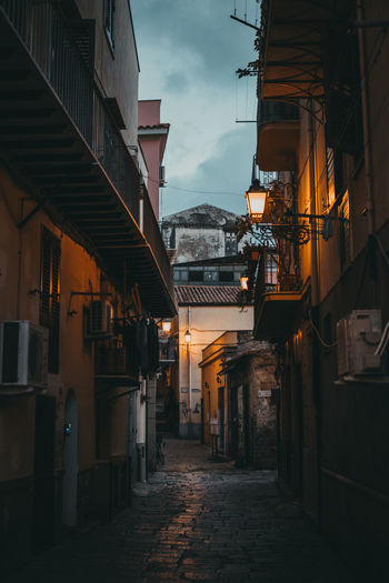 Alley Amidst Buildings In City At Dusk