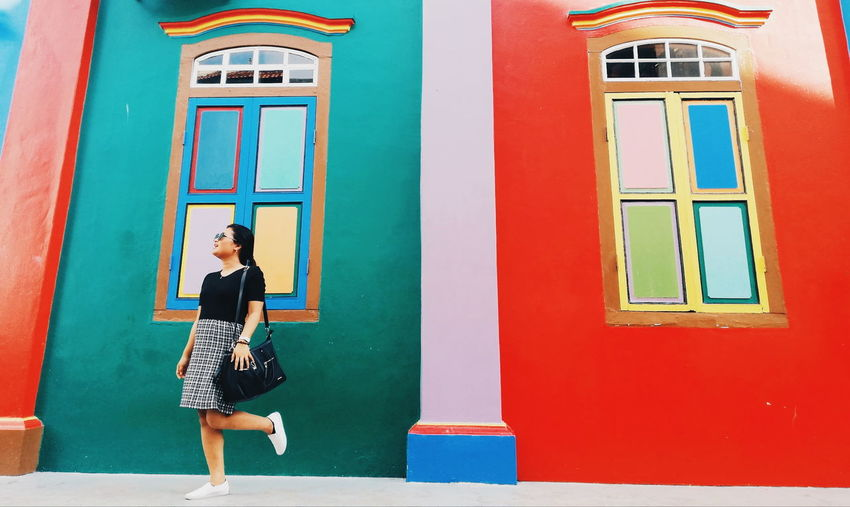 Woman Posing Against Colorful House